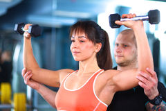 Beautiful woman at the gym exercising with her Stock Photos