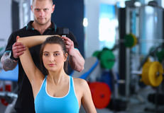 Beautiful woman at the gym exercising with her Royalty Free Stock Images