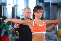 Beautiful woman at the gym exercising with her Royalty Free Stock Image