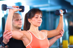 Beautiful woman at the gym exercising with her Royalty Free Stock Photography