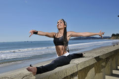 Beautiful woman in gymnist pose on beach. Young woman in gymnist pose Royalty Free Stock Photography