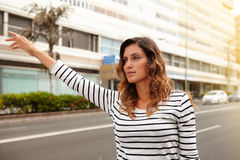 Beautiful woman hailing a cab during the day. Waist up portrait of a beautiful woman of caucasian ethnicity hailing a cab during the day Royalty Free Stock Photos