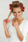 Beautiful Woman With Hair Curlers, Hair Rollers On Healthy Curly. Hairdressing. Happy Woman Applying Hair Rollers On Beautiful Healthy Blonde Hair. Attractive stock images