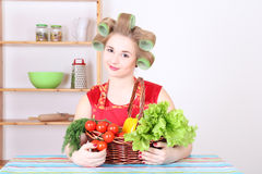 Beautiful woman with hair curlers in the kitchen Royalty Free Stock Photography