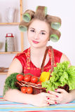 Beautiful woman with hair curlers in the kitchen Royalty Free Stock Photos