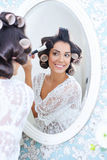 Beautiful woman in hair curlers puts on morning makeup Royalty Free Stock Photo