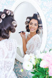 Beautiful woman in hair curlers puts on morning makeup Royalty Free Stock Images