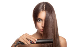 Beautiful woman with hair iron. Royalty Free Stock Images
