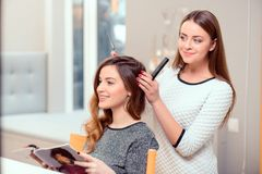 Beautiful woman in hair salon. Going for a change of style. Young beautiful women discussing hairstyling with her hairdresser holding a comb and scissors while Stock Photos