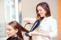 Beautiful woman in hair salon. Stylish by professionals you can trust.  Mirror reflection of a young beautiful hairdresser doing her clients hair with a hair Stock Image