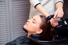 Beautiful woman in hair salon. Wash away the stress. Cropped shot of a young women having her hair washed at a professional hair salon Royalty Free Stock Image