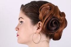 Beautiful woman with hairdo and earrings. In studio, profile, focus on hairdo Royalty Free Stock Photography
