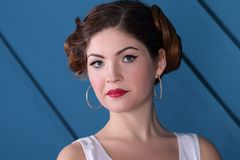 Beautiful woman with hairdo poses in blue studio. Close up portrait Royalty Free Stock Image
