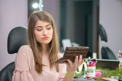 Beautiful woman with hairstyle and makeup looking at the mirror in beauty salon stock photo