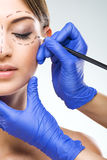 Beautiful woman half face photo plastic surgery, plastic surgeon hands.  Stock Photo