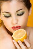Beautiful woman with half of lemon, closed eyes. Gorgeous young woman wearing colorful make-up and holding half of lemon Royalty Free Stock Images