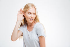 Beautiful woman with hand at the ear to hear better Royalty Free Stock Photo