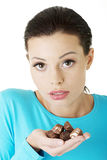 Beautiful woman with hand full of chocolates Royalty Free Stock Photos