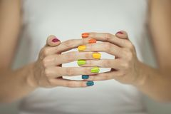 Beautiful woman hands with colorful rainbow nail polish stock photography