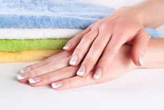 Beautiful woman hands with french nails manicure on colorful towels. Femininity and Beauty concept image. Close up Royalty Free Stock Photography