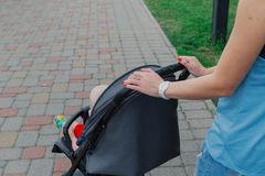 Beautiful woman hands on the handle of a pram. stock photo
