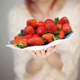 Beautiful woman hands holding a plate with strawberries in her hands. Sensual studio shot can be used as background Stock Photos