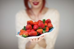 Beautiful woman hands holding a plate with strawberries in her hands. Sensual studio shot can be used as background Royalty Free Stock Photos