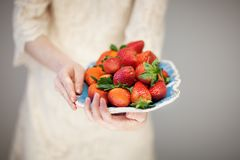 Beautiful woman hands holding a plate with strawberries in her hands. Sensual studio shot can be used as background Stock Photography