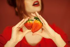 Beautiful woman hands holding some strawberries in her hands. Sensual studio shot can be used as background stock photography