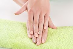 Beautiful girl hands with orange manicure. Beautiful woman hands with orange manicure on finger nails on green towel in beauty studio. Close up, selective focus royalty free stock photos