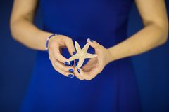 Beautiful woman hands with perfect nail polish holding little starfish in front of blue dress royalty free stock photos