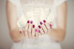 Beautiful woman hands with perfect pink nail polish holding giant royalty free stock images