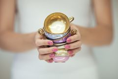 Beautiful woman hands with perfect pink nail polish holding little vintage tea cups. Romantic shabby chic mood, can be used as background stock photos