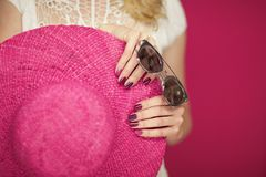Beautiful woman hands with perfect pink nail polish holding pink sunhat and sunglasses, happy beach mood. Can be used as background royalty free stock image