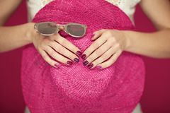 Beautiful woman hands with perfect pink nail polish holding pink sunhat and sunglasses, happy beach mood. Can be used as background royalty free stock images