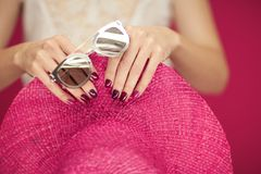 Beautiful woman hands with perfect pink nail polish holding pink sunhat and sunglasses, happy beach mood. Can be used as background royalty free stock photography