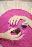 Beautiful woman hands with perfect pink nail polish holding sunhat and sunglasses, happy beach mood. Beautiful woman hands with perfect pink nail polish holding stock photos