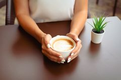 Woman hands holding cappucino or latte art. Beautiful woman hands with perfect white manicure holding a white cup of cappucino or latte art at the table in a stock photography