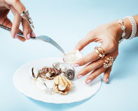 Beautiful woman hands with pink manicure holding plate with pearls and sea shells, luxury jewelry concept Stock Photography