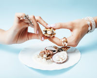 Beautiful woman hands with pink manicure holding plate with pearls and sea shells, luxury jewelry concept Royalty Free Stock Photo