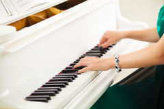 Beautiful woman hands playing music on white grand piano. Beautiful woman hands playing concert on white grand piano royalty free stock images