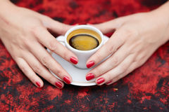 Beautiful woman hands with red manicure and cup of fresh coffee Royalty Free Stock Photography