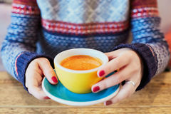 Beautiful woman hands with red manicure and cup of fresh hot coffee on wooden table Stock Images