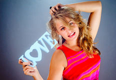 The beautiful woman in hands shows a word love Stock Photography
