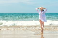 Beautiful woman with hands up relaxing on the sand beach with sea view, enjoying the summer breeze and sound of the waves. Travel and tourism concept stock photos