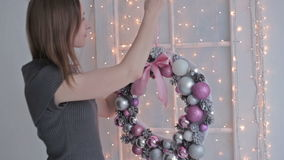 A beautiful woman hanging a Christmas wreath on. Her home, HD stock video footage