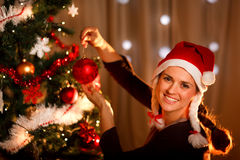 Beautiful woman hanging toy on Christmas tree Stock Photo