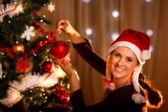 Beautiful woman hanging toy on Christmas tree Stock Photo