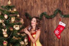 Beautiful woman hangs up the ball on the Christmas tree Christma Royalty Free Stock Photography