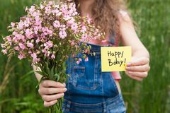 Beautiful woman with Happy birthday card and bouquet of pink flowers. Anniversary concept royalty free stock image